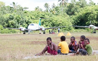 alt='Children watch as planes are stowed at Guasopa airstrip on Woodlark Island'